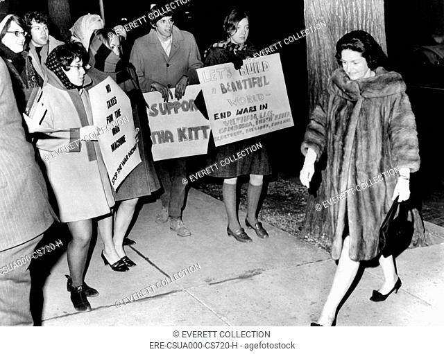 Lady Bird Johnson walks past a group of youthful anti-war demonstrators. The First Lady was attending the reopening of the WomanÆs National Democratic Club...