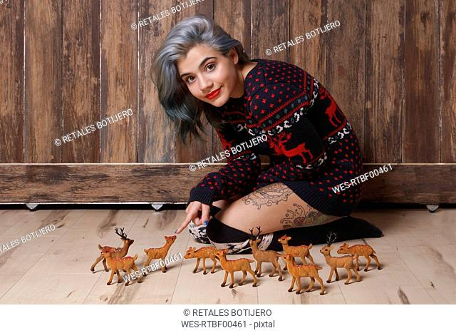 Portrait of smiling young woman wearing patterned knit pullover sitting on the floor with deer figurines