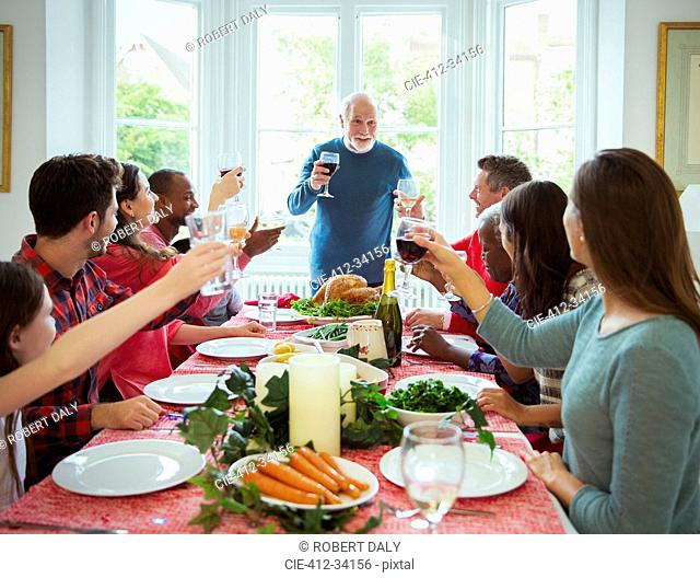 Grandfather making toast with wine at Christmas dinner table