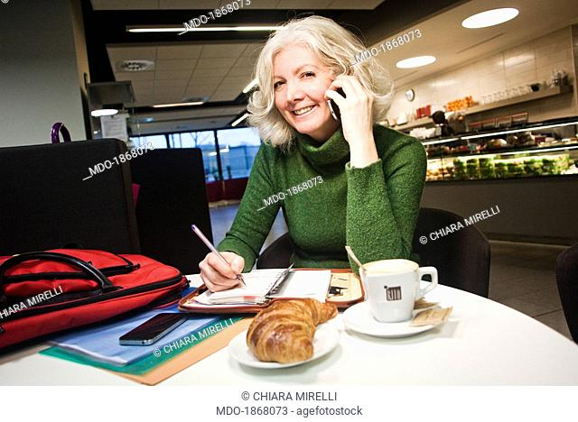 Woman sitting at the table of a coffee house and speaking over the phone in front of an open organizer, a cappuccino and a croissant