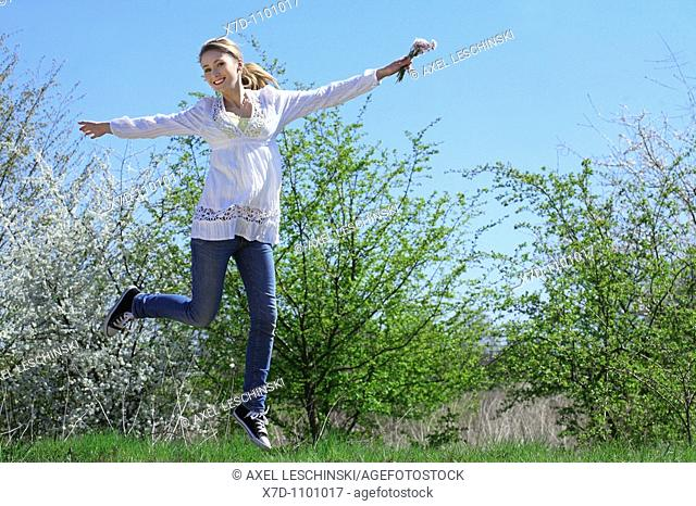 Young brunette woman enjoying a walk in spring landscape jumping in the air