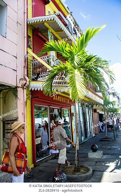 Older mature senior blond woman shopping, looking at front stores, looking at clothing, pointing at beautiful dress, while strolling the streets of Fort De...