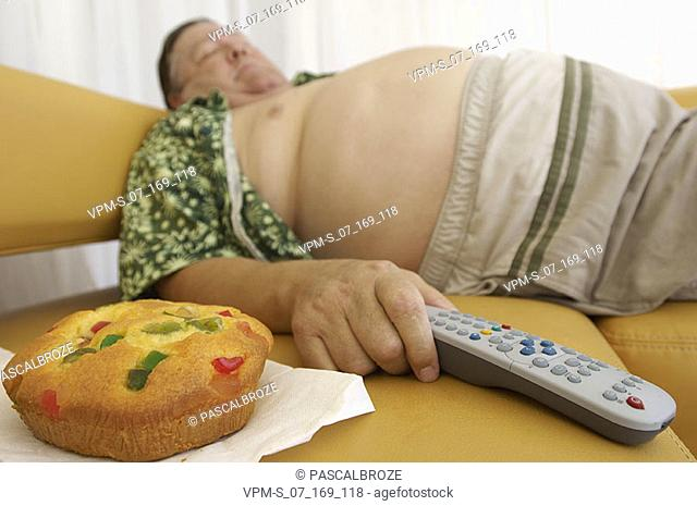 Side profile of a mature man sleeping and holding a remote control