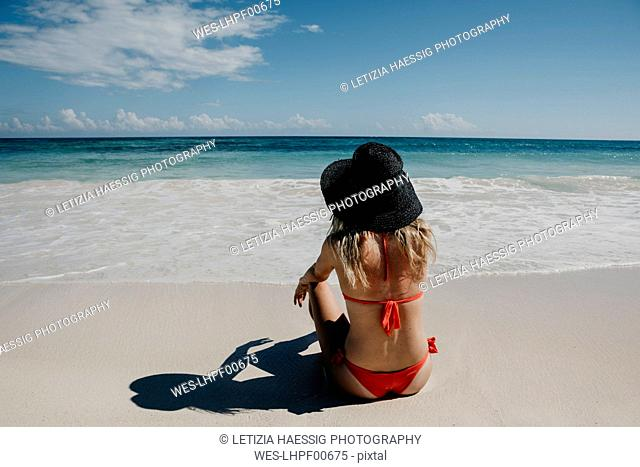 Mexico, Quintana Roo, Tulum, young woman with hat lying on the beach