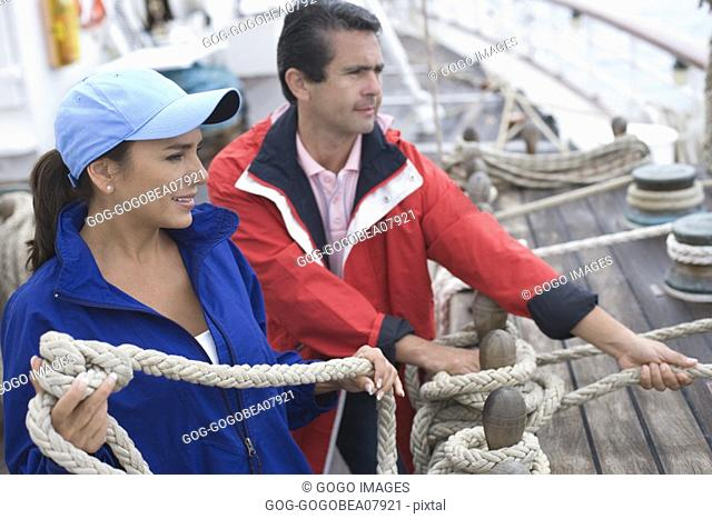 Couple untying ship's rigging