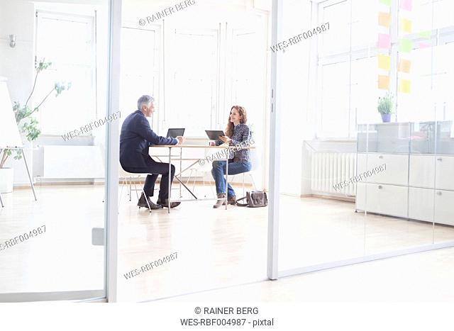 Businessman and woman with laptop and tablet in bright office
