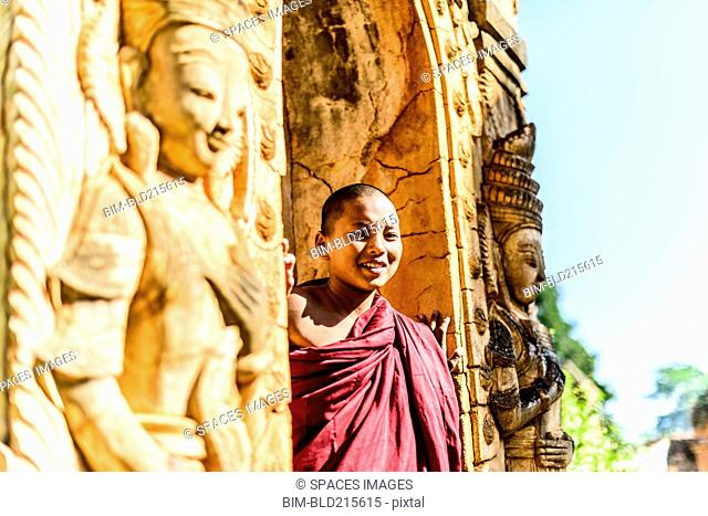 Asian monk-in-training peering around carved temple walls