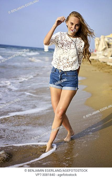 Greece, Crete, Malia, woman walking on the beach