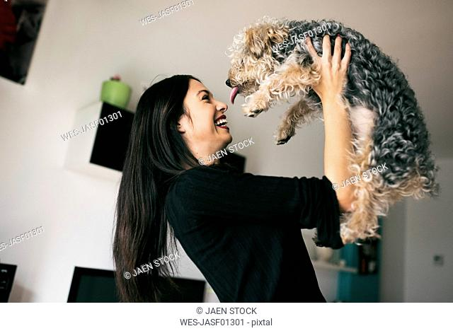 Happy young woman with her dog at home