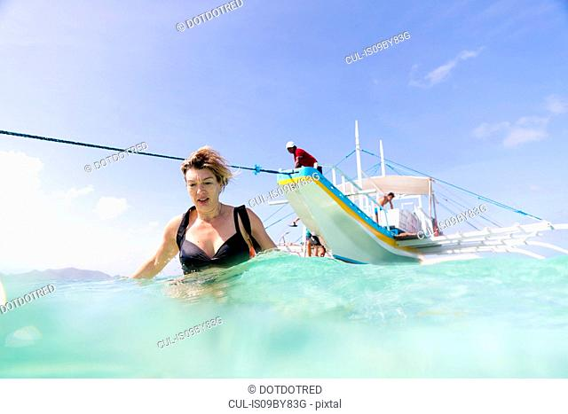 Woman walking away from boat moored in sea, Ginto island, Linapacan, Philippines