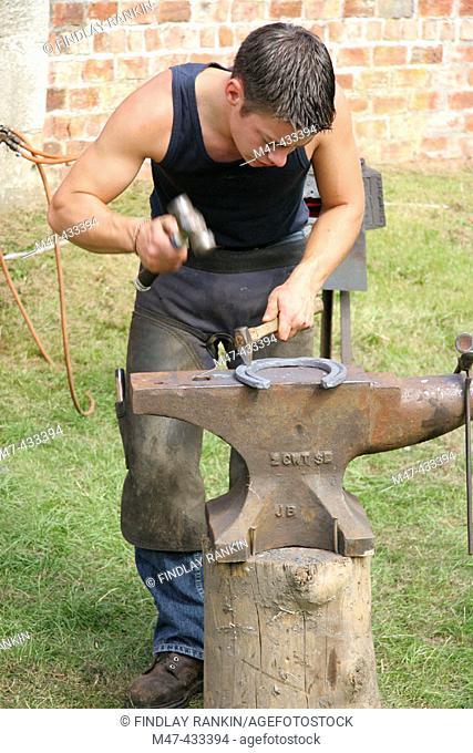 Blacksmith farrier making a horseshoe