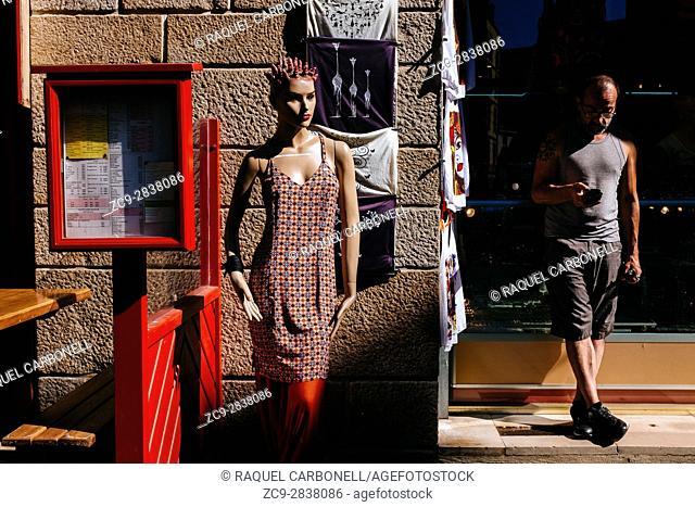 Man standing outside clothes shop window next to mannequin, Saint Malo, Ille-et-Vilaine, Brittany, France