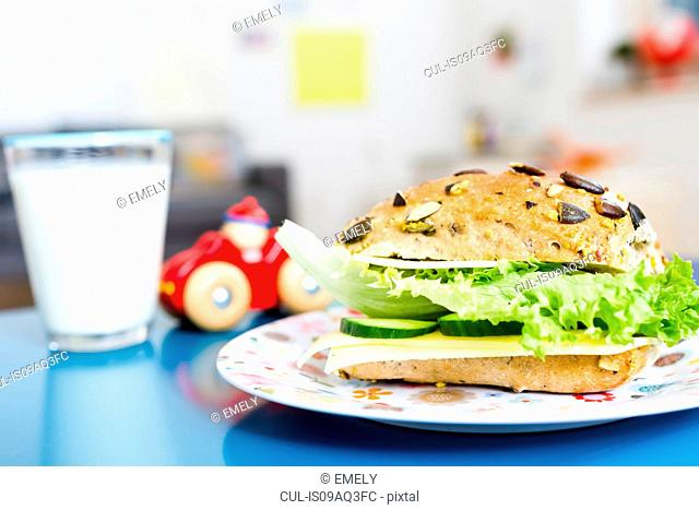 Sandwich, glass of milk, toy car on table