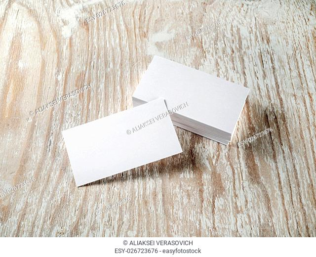 Photo. Blank business cards with soft shadows on light wooden background. Template for ID. For design presentations and portfolios