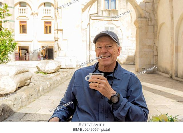 Smiling older Caucasian man drinking coffee in garden