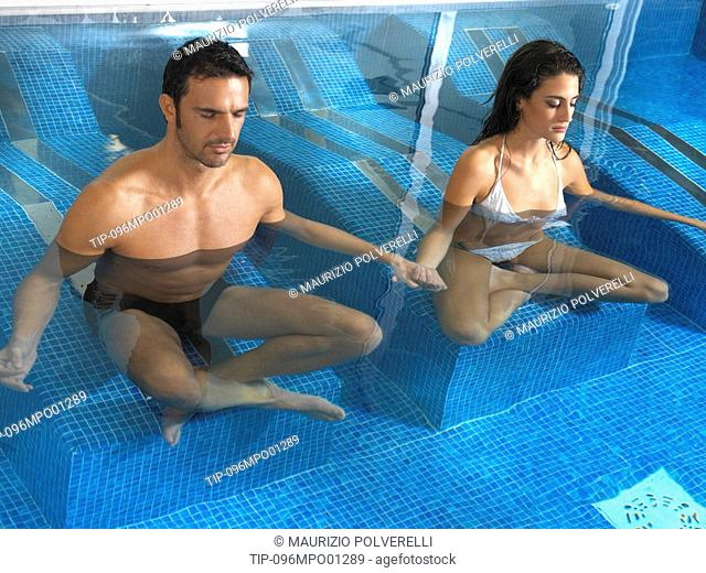 Couple in swimming pool doing yoga