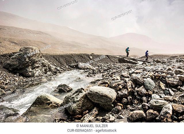 Two female hikers crossing river footbridge, Fil de Cassons, Segnesboden, Graubunden, Switzerland