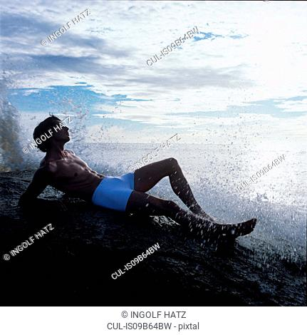 Man lying on rock in sea looking away, China Bay, Sri Lanka, Asia