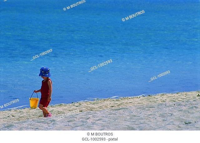 Child with bucket on the beach, Mauritius