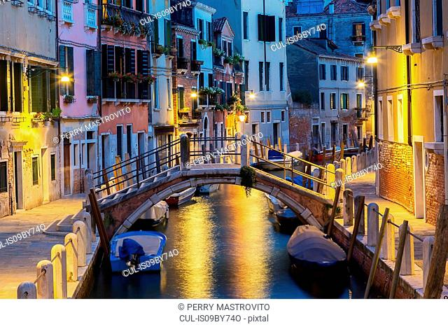 Moored boats and footbridge over Rio de la Toletta Canal, old architectural style residential buildings at dusk, Dorsoduro district, Venice, Veneto, Italy