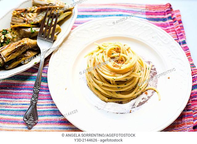 Botargo with spaghetti and cooked artichokes