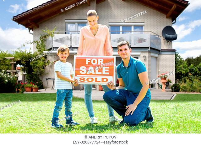 Portrait Of Happy Young Family With A Sale Sign Outside Their Home