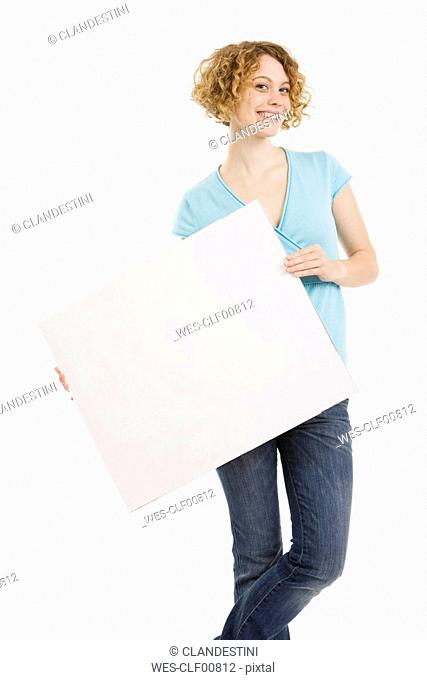 Young woman holding blank cardboard, smiling, portrait