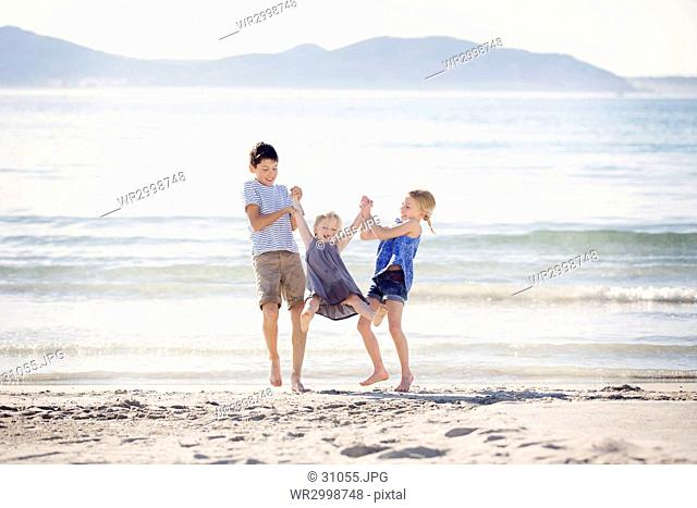 Boy and girl standing on a sandy beach by the ocean, swinging young girl