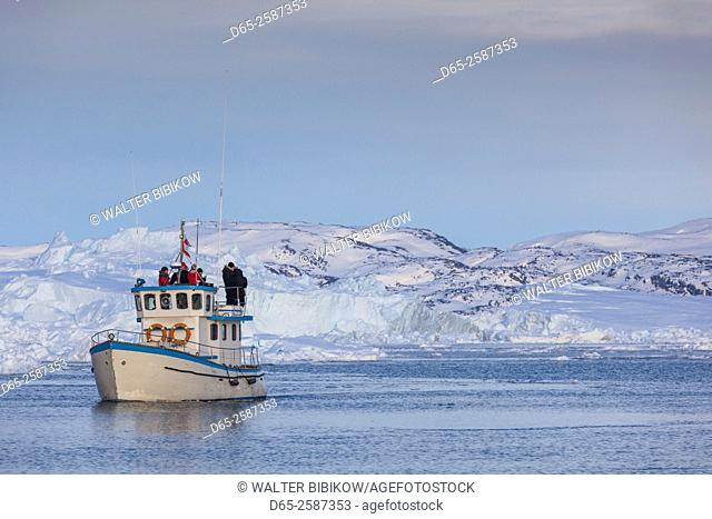 Greenland, Disko Bay, Ilulissat, fishing boat in floating ice at sunset