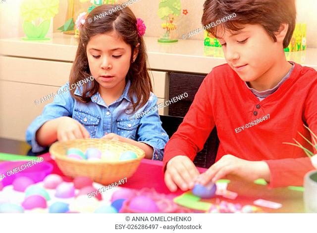 .Portrait of brother and sister painting traditional Easter eggs in different colors at home, with pleasure preparing to religious spring holiday