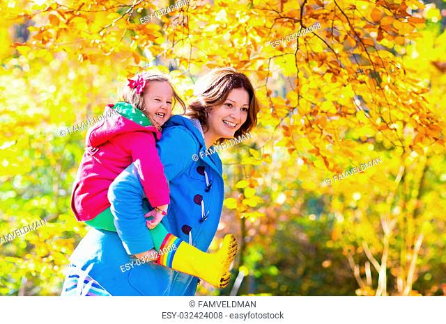 Mother and daughter play in autumn park. Parent and child walk in the forest on a sunny fall day. Children playing outdoors with yellow maple leaf