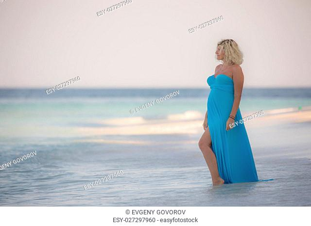 Beautiful pregnant woman is standing on the amazing Maldivian beach