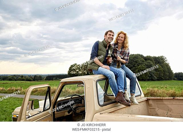 Couple sitting on pick up truck having a beer