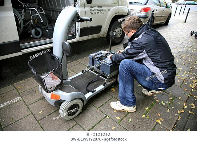 man changing power supply of mobility scooter