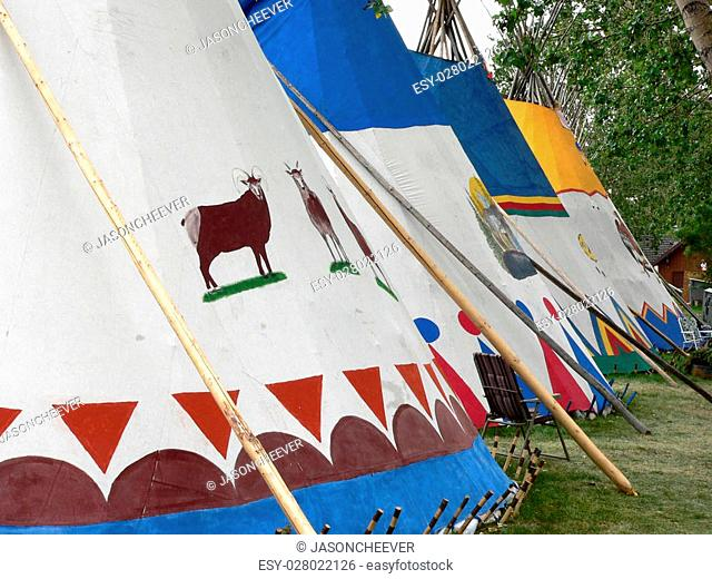 Village during Calgary Stampede. CalgarJuxtoposition of traditional tepees and modern lawn chairs at Indian y, Alberta, Canada