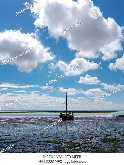 A flat-bottemed sailing boat at dry tide-land