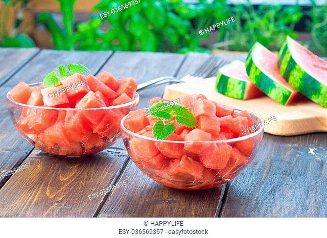 Watermelon cut in small cubes and served in two glas dishes on wooden table in rustic style