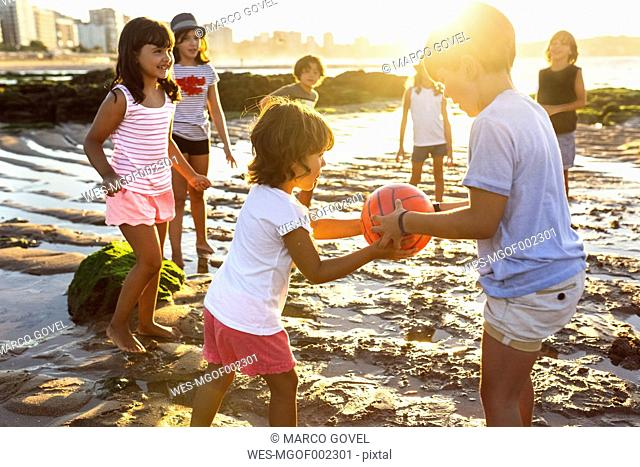 Kids playing with a ball on the beach at sunset