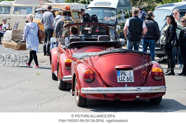 01 May 2019, Lower Saxony, Hanover: A VW Beetle with trailer drives at the 36th May Beetle Meeting on a fair parking lot