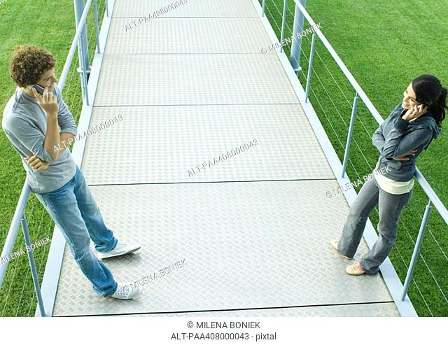 Teenage couple standing face to face on walkway, using cell phones, full length, high angle view