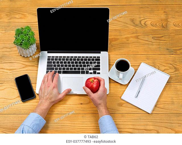 High angled view of male hand holding apple while typing on computer keyboard