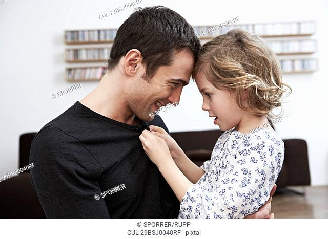 Girl buttoning up fathers shirt