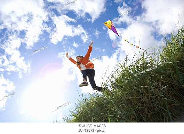 Girl 7-9 years flying kite outdoors, low angle view
