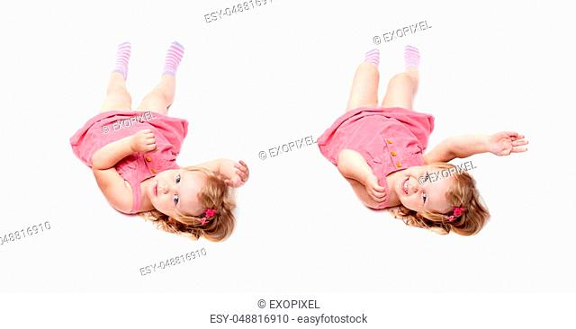 Young little girl with curly hair in pink dress lying over isolated white background