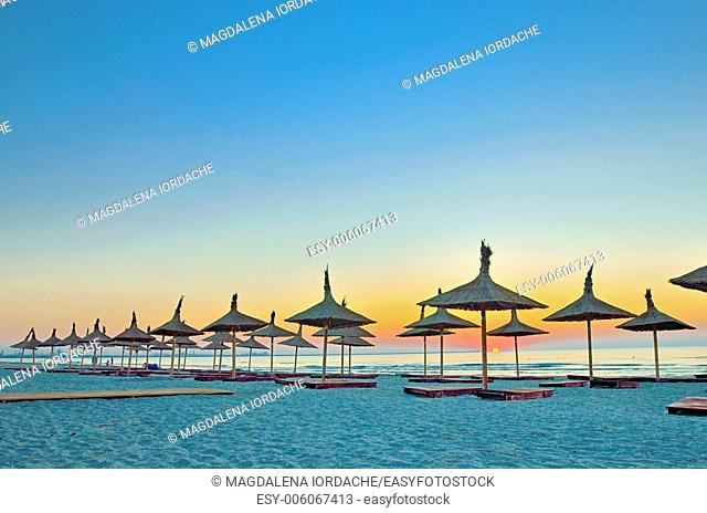 empty sandy beach with umbrellas and beach beds and sunrise
