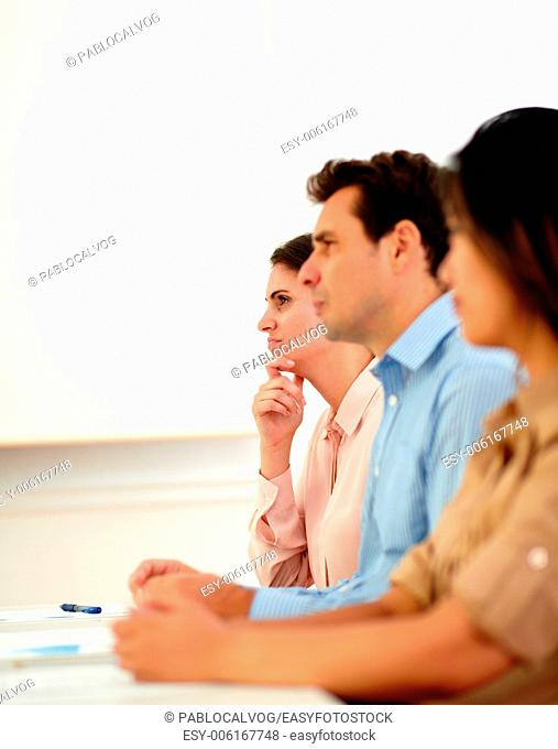 Portrait of handsome businessman on blue shirt listen during a meeting while sitting between two beautiful businesswoman on workplace