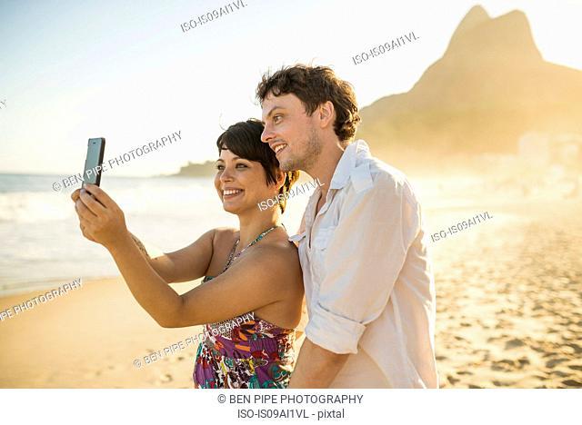 Young couple self-photographing, Ipanema Beach, Rio, Brazil