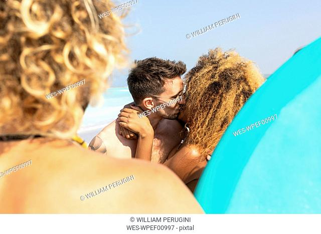 Couple on the beach with friends, tkissing each other