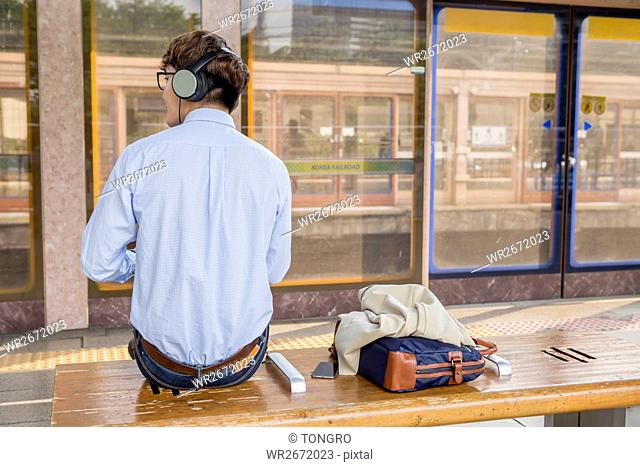 Businessman with headphones waiting for train