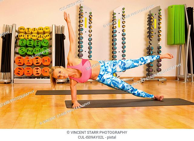 Woman in gym exercising on yoga mat